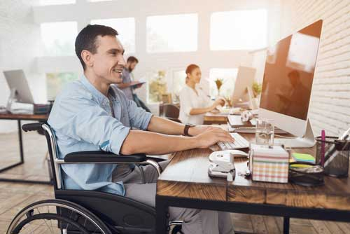 A disabled man working on a computer.
