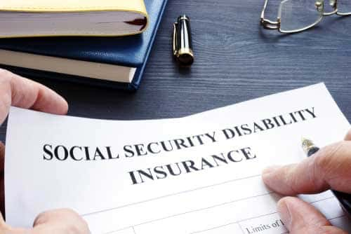 An individual signing a social security disability insurance document.