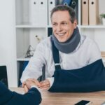 worker-in-neck-brace-with-brokenarm-and-businessma-7JZ5EFY-1